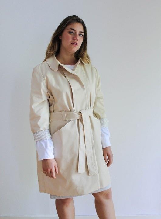 Jeune femme ronde portant un trench-coat beige